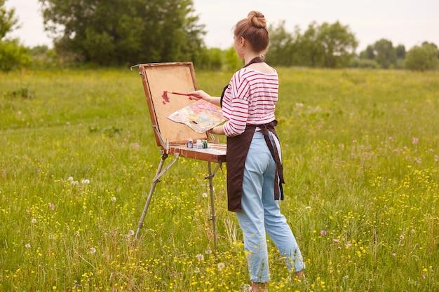 Het openluchtschot van jonge slanke vrouwenkunstenaar die achteruit bevinden zich, houdend borstel en palet van kleuren, schildert beeld in aard in de zomer, vrouwelijk tekeningslandschap. concept van hobby en creativiteit.