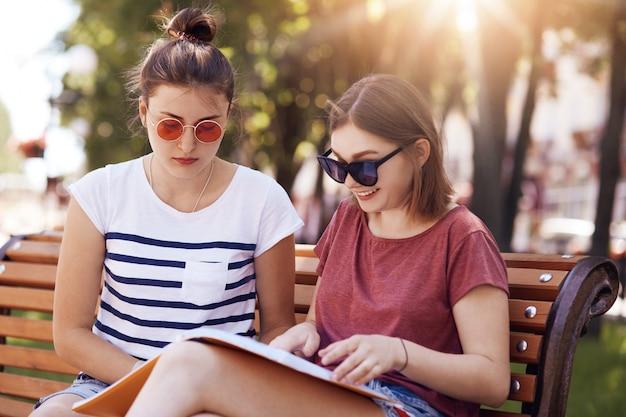 Het openluchtschot van twee vrouwelijke vrienden draagt zonnebril