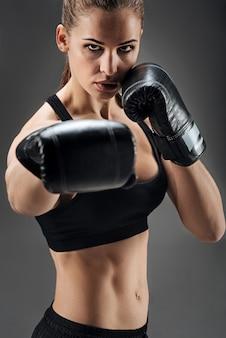 Het opgetogen vrouw stellen met bokshandschoenen