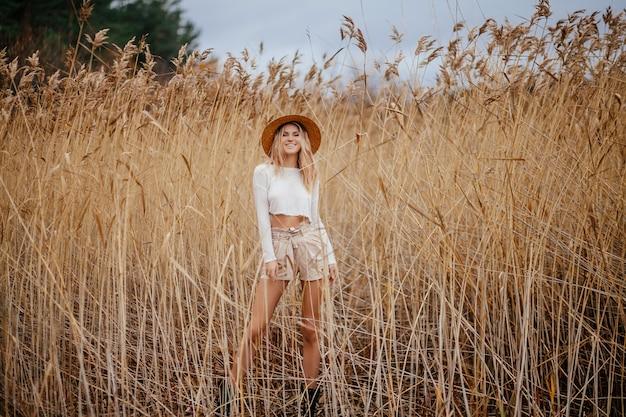 Het opgewekte blonde gelukkige meisje van de safaristijl in een strohoed loopt op aard onder het riet.