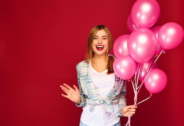 Het opgewekte jonge vrouw stellen met roze luchtballons
