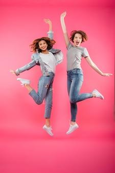 Het opgewekte twee damesvrienden springen geïsoleerd