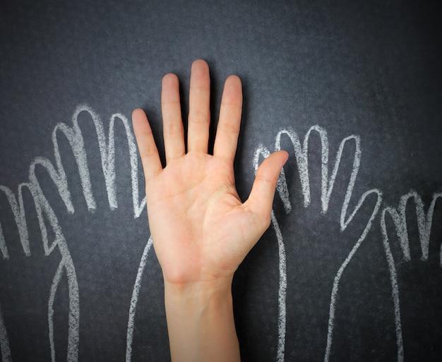 Het opheffen van handen tegen bordachtergrond. handkrabbel op schoolbordachtergrond die wordt getrokken.