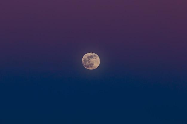 Het opkomen van de volle maan. zonsondergangtijd in de schemeringhemel.