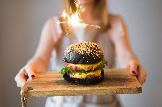 Het opperhoofd houdt een houten snijplank vast met een zwarte hamburger.