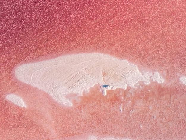 Het oppervlak van een roze meer met zouteilandjes