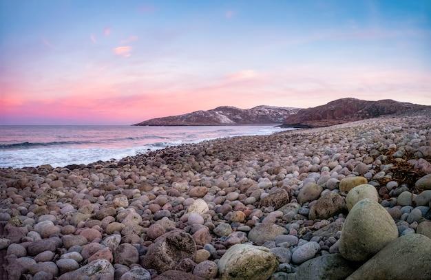 Het oppervlak van het strand aan de noordelijke oceaan is bedekt met grote gepolijste ronde stenen van grijze kleur van verschillende groottes. teriberka. rusland.