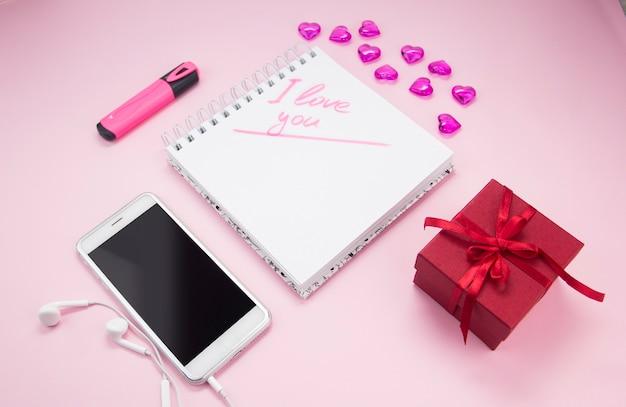 Het opschrift ik hou van je in een notitieboekje naast een cadeau en een smartphone valentijnsdag
