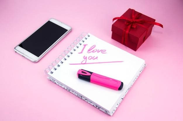 Het opschrift ik hou van je in een notitieboekje naast een cadeau en een smartphone Premium Foto