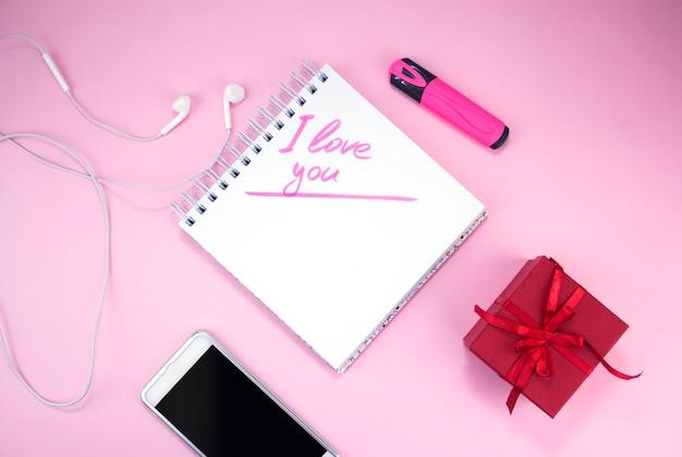 Het opschrift ik hou van je in een notitieboekje naast een cadeau en een smartphone