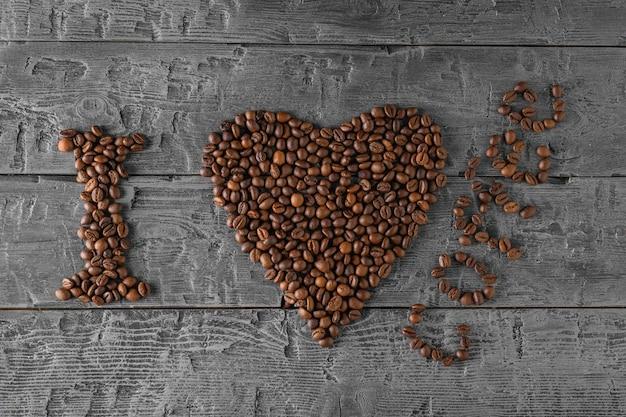 Het opschrift ik hou van koffie gemaakt van gebrande koffiebonen op een zwarte houten tafel.