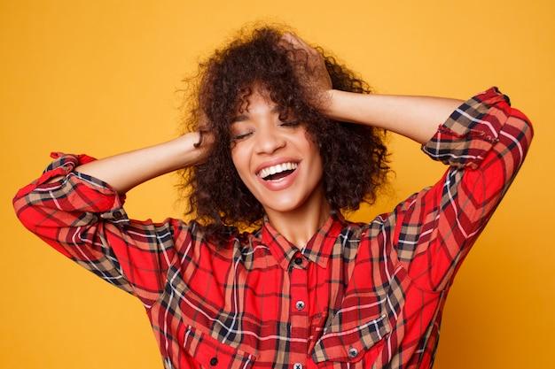 Het optimistische lachende zwarte stellen in studio op oranje achtergrond. ontspannen krullend vrouwelijk model dat van het leven geniet.