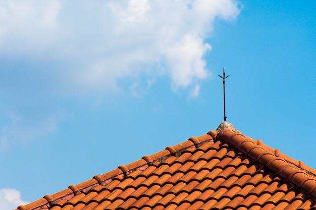 Het oranje bakstenen dak met bliksempalen bovenop het dak