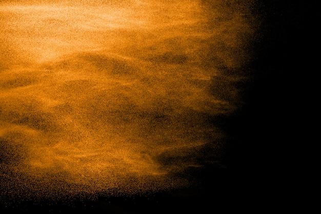 Het oranje kleurenpoeder ploetert op zwarte achtergrond.