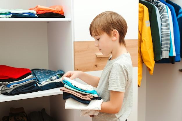 Het organiseren van kleren in kleerkast, close-up. kid stapel kleren op de plank zetten.