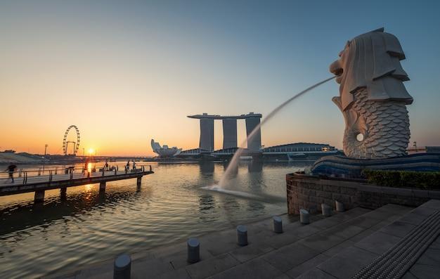 Het oriëntatiepunt merlion van singapore met zonsopgang