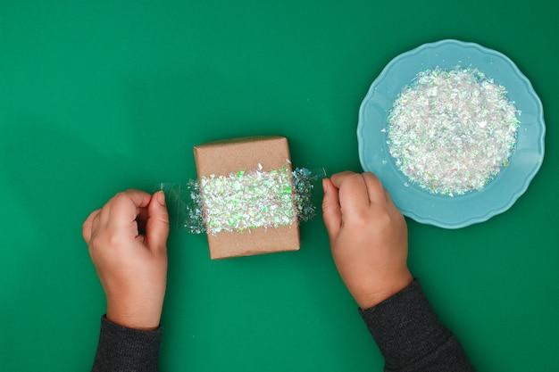 Het originele ontwerp van een kerstcadeau van ambachtelijk papier, scotch tape en geslepen glanzend plastic