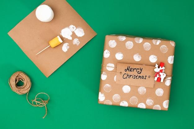 Het originele ontwerp van een kerstcadeau van ambachtelijke papier, witte verf, een stempel van aardappelen.