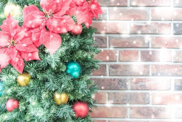Het ornament van kerstmis met gekleurde ballen en een bakstenen muur