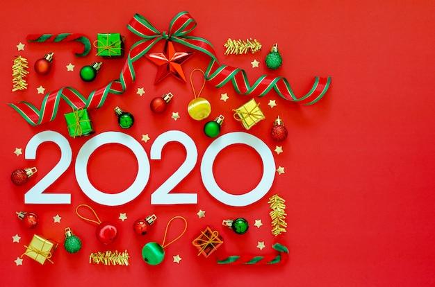 Het ornamentdecoratie van het nieuwjaar plaatste als giftdoos met lint op rode achtergrond. plat lag minimale vakantie.