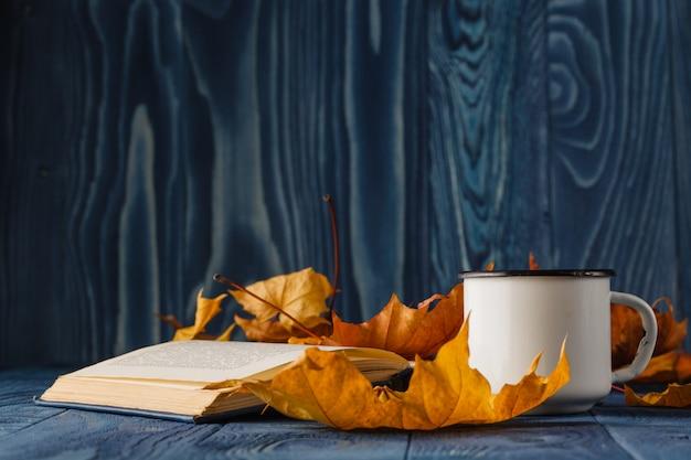 Het oude boek van het kop thee verstand en de herfstbladeren op houten lijst