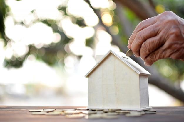 Het oude de holdingsmuntstuk van de hand laten vallen om huis op houten plank en boom bokeh achtergrond te modelleren