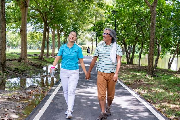 Het oude paar ontspant na het joggen. ze houden hun handen vast en glimlachen.