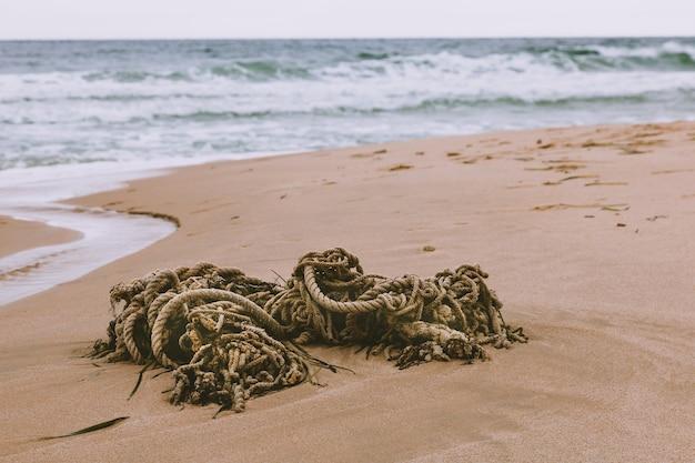 Het oude touw ligt op het zand op het strand tegen de zee en golven.