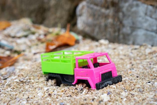 Het oude vrachtwagenspeelgoed is verlaten op het strand. het wordt een vuilnis op zee.
