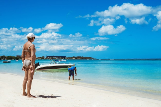 Het oude vrouw zonnebaden die op zand blijven, die oceaan bekijken