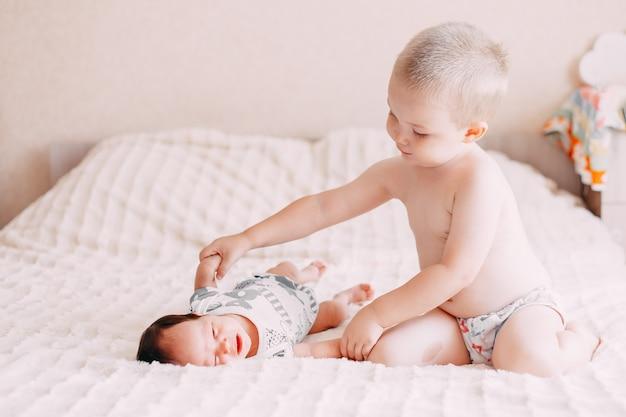 Het oudere de jongenszoon van de broer blonde spelen met kleine babyzuster