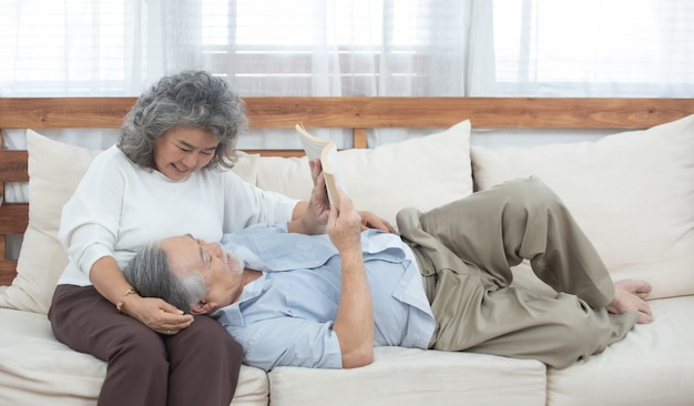 Het oudere paar zit thuis op laag gelezen boek