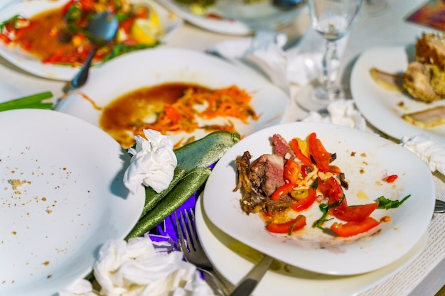 Het overgebleven eten en de vuile vaat op de tafel van het restaurant. restjes die over zijn na het feest.