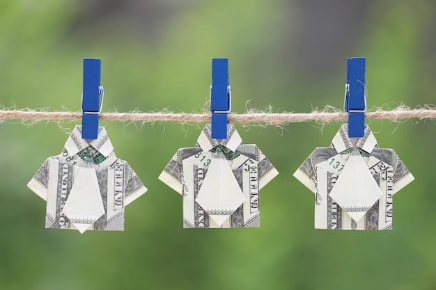 Het overhemd van de origamidollar bij het hangen van aard groene achtergrond
