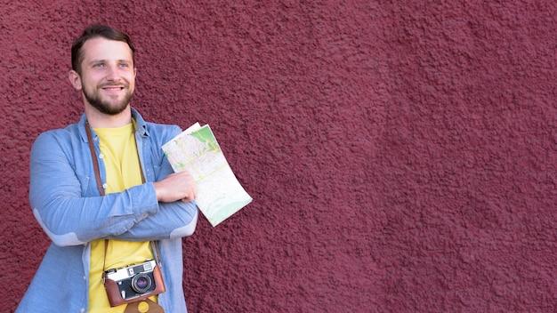 Het overwegen van jonge glimlachende de holdingskaart die van de reizigersfotograaf zich dichtbij geweven muurachtergrond bevinden