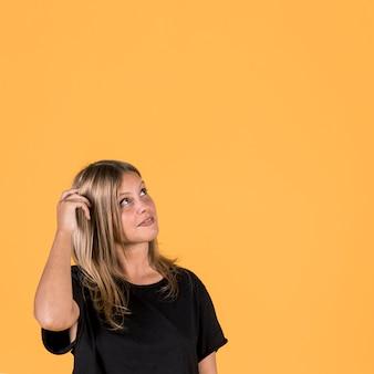 Het overwegen van jonge vrouw die omhoog over gele achtergrond kijkt