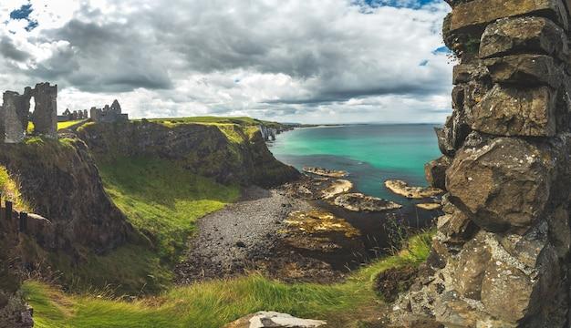 Het overzicht van dunluce castle tot de ierse baai, overweldigend landschap van noord-ierland epic