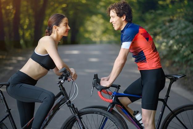 Het paar berijdende fietsen van sporten in de zomerbos