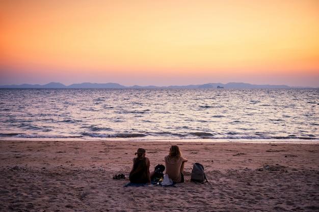 Het paar bij strand ziet overzees en schemeringhemel