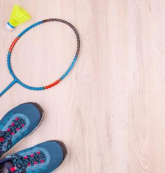 Het paar blauwe damessneakers, badmintonracket en shuttle op wit houten oppervlak