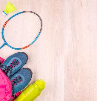 Het paar blauwe damessneakers en fles in roze rugzak, badmintonracket en shuttle op wit houten oppervlak