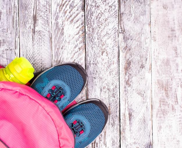 Het paar blauwe damessneakers in roze rugzak en sportfles voor water op wit houten oppervlak
