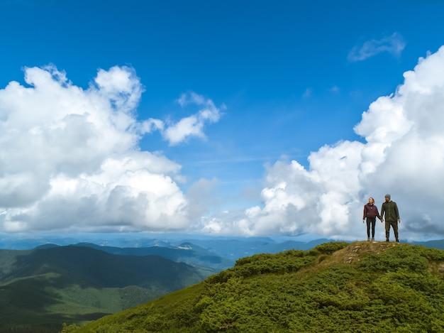 Het paar dat op de berg staat tegen het wolkenlandschap