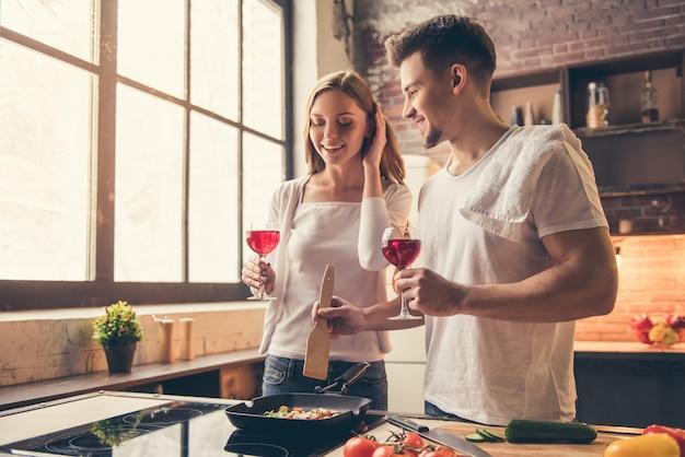Het paar drinkt wijn en glimlacht terwijl samen het koken