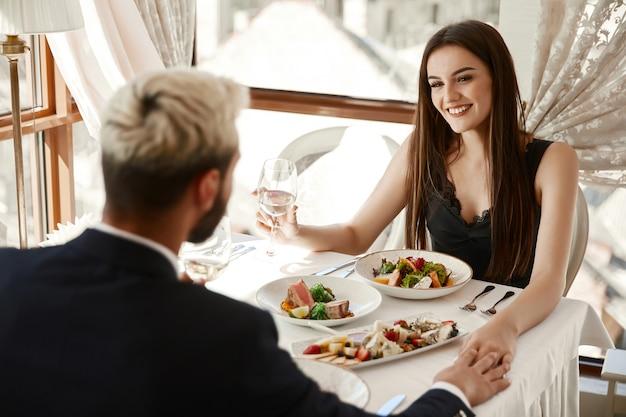 Het paar drinkt witte wijn bij het romantische diner in het restaurant en hand in hand