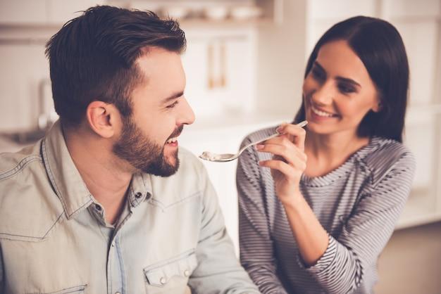 Het paar eet en glimlacht terwijl het zitten in keuken