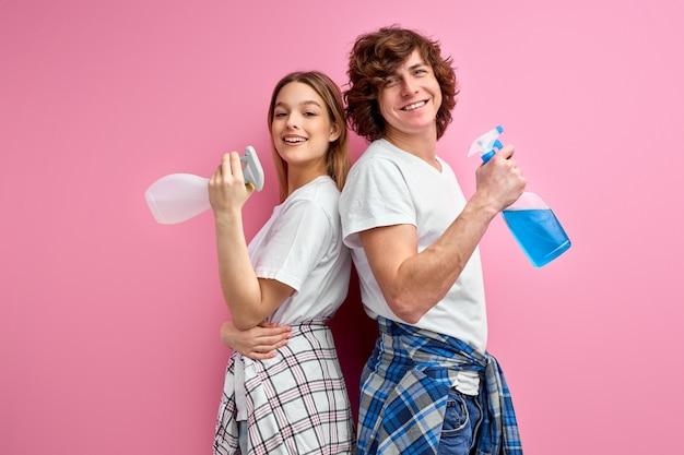 Het paar gebruikt detergentia voor het schoonmaken geïsoleerd op roze studioachtergrond.