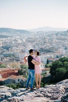 Het paar heeft een date op de top van de heuvel met een panoramisch uitzicht op de stad elkaar kussen