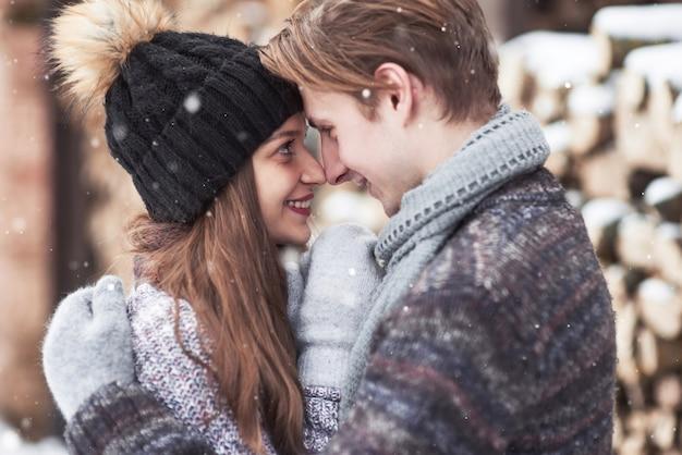 Het paar heeft plezier en lacht. kus. jong hipsterpaar die elkaar in de winterpark koesteren.
