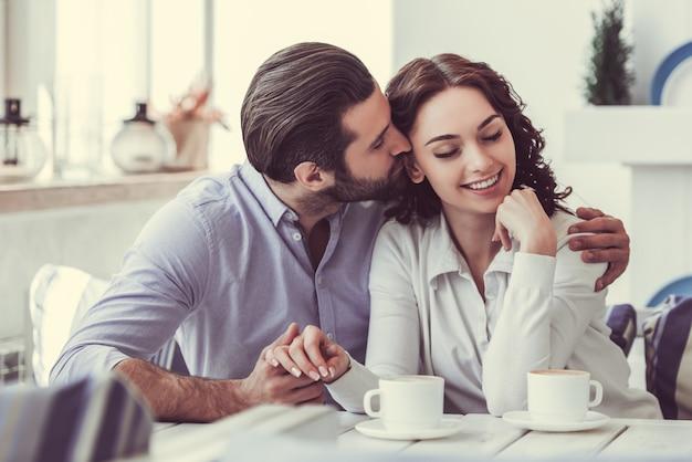 Het paar houdt handen en glimlacht terwijl het rusten in koffie.